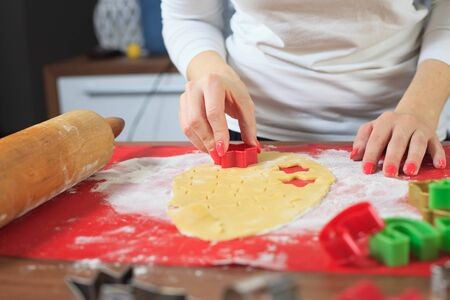 Young hands cutting ginger dough at modern kitchen