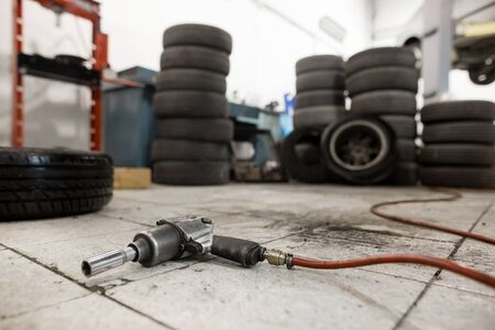 Vacuum gun for replacing wheels of the car on the floor, transportation concept, car service center