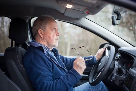 Senior man putting on glasses before driving, his eyesight is not good, safety and transportation concept