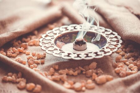 Frankincense burning on a hot coal. Frankincense is aromatic resin, religious rites, incense and perfumes, incense smoke Stock Photo