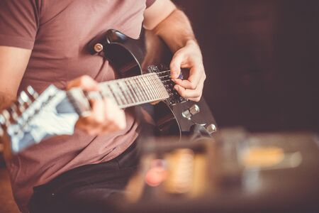 Close up hand of young man playing on a professional, black electric guitar, music instrument, entertainment, lifestyle
