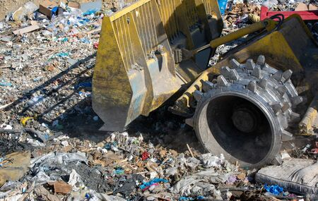 Close up of bulldozer working on the huge landfill or garbage dump pile, pollution concept