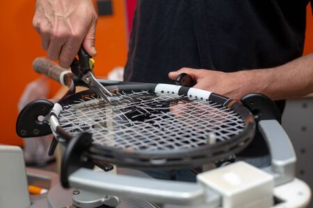 Process of stringing a tennis racket in a tennis shop, sport and leisure concept
