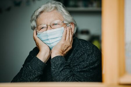Senior woman with medical mask at the home during coronavirus, covid-2019 pandemic, stay home