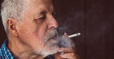 Senior man smoking cigarette outside, the cigarette addiction, unhealthy concept, bad habit