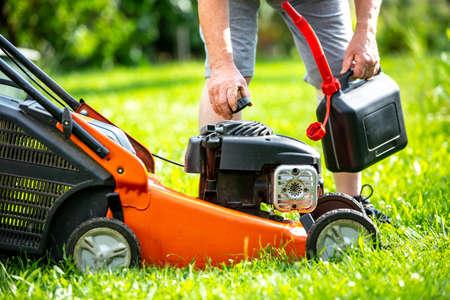 Man refueling the lawnmower on his huge garden, gardening concept