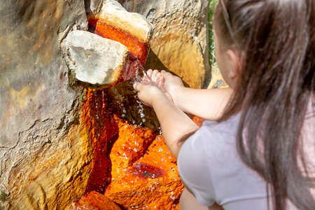 Young woman taps the water from spring of mineral water, ferruginous water with a high mineral content
