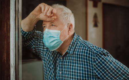 Senior man quarantined by coronavirus, covid-2019 at a home, looking outside by the windown, stay at home