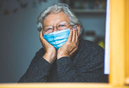 Senior woman quarantined by coronavirus, covid-2019 at a home, looking outside by the windown, stay at home Stockfoto