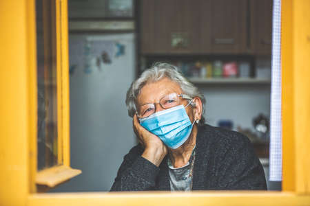Senior woman quarantined by coronavirus, covid-2019 at a home, looking outside by the windown, stay at home