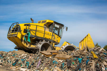Huge bulldozer working at the huge landfill or garbage dump, pollution concept