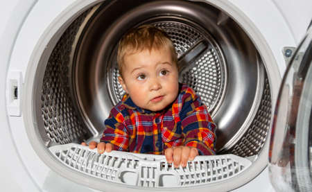 Close up of portrait lovely kid looks out from the washing machine, funny concept