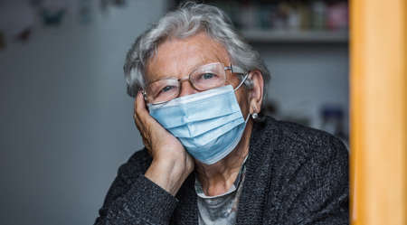 Close up of an old senior woman watching out from a window during covid-19 or coronavirus pandemic, quarantine at home