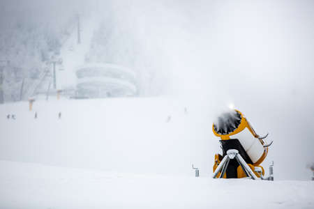 Snow cannon, machine or gun snowing the slopes or mountain for skiers and snowboarders
