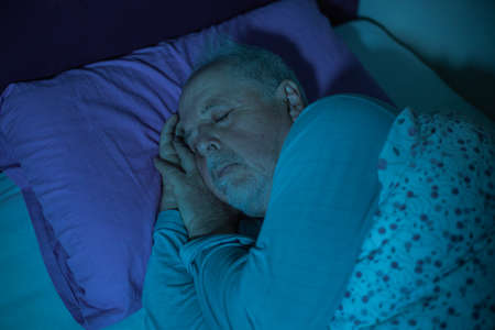 Senior man sleeping in the middle of the night in a bed, deep sleep Standard-Bild