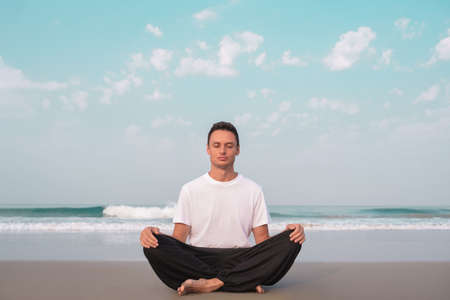 the guy sits on the seashore in the lotus position and meditates.