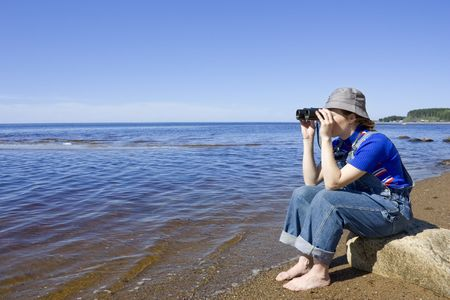Woman with binoculars looking out to sea. photo