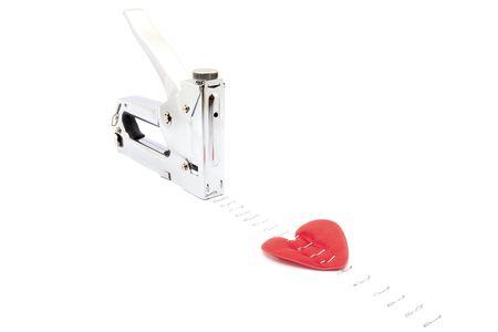 broken unity:  Heart stapler nailed to the horizontal surface.