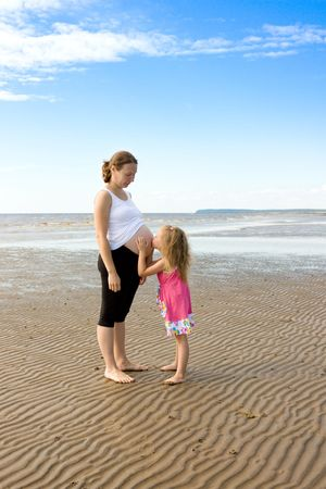 Daughter on the beach obnmaet pregnant mother.Mother and daughter photo