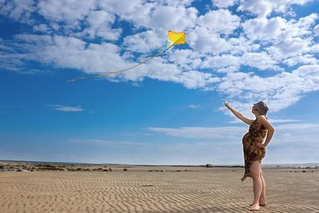 A pregnant woman runs into the sky kite photo