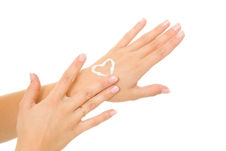 Cream in a female hand on heart. Imagens