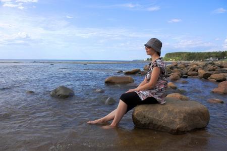 A woman sitting on the beach. photo