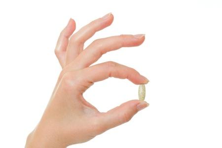 vitamina a: La c�psula en la mano sobre un fondo blanco.