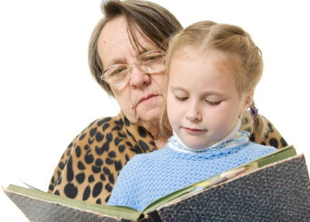 Grandmother granddaughter reading a book on a white background photo