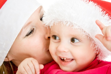 Happy Christmas mother kissing daughter on a white background.