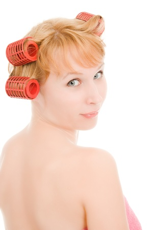A woman in curlers looking back on a white background. photo