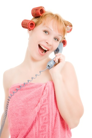 A woman in curlers talking on the phone on a white background. Stock Photo - 11181736