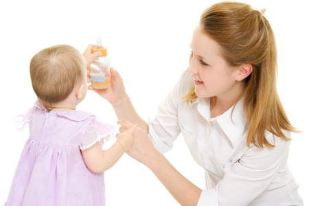 The woman gives the baby a bottle of infant formula. photo