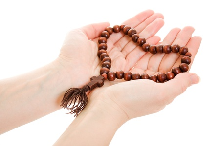 A girl holds a rosary in his hands on a white background. photo