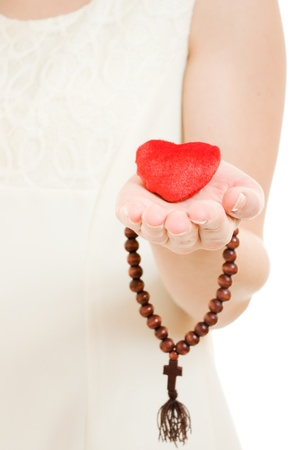 Woman holds the heart and the rosary in his hand on a white background. photo