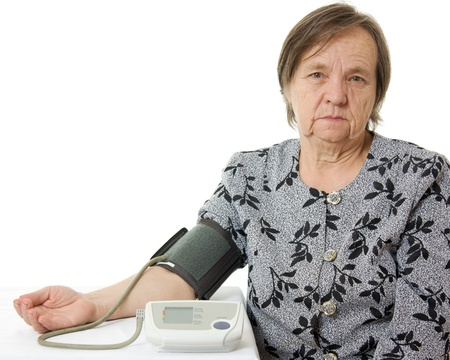 An elderly woman with a sphygmomanometer on a white background. photo