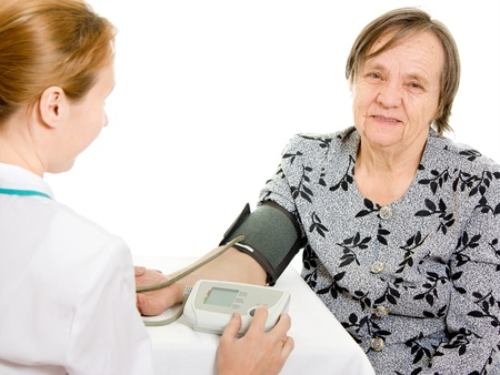 The doctor and an elderly woman with a sphygmomanometer on a white background. photo