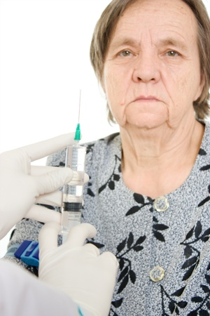 The doctor makes vaccination an old woman. photo