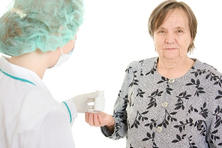 The doctor takes a bottle of pills the old woman. photo