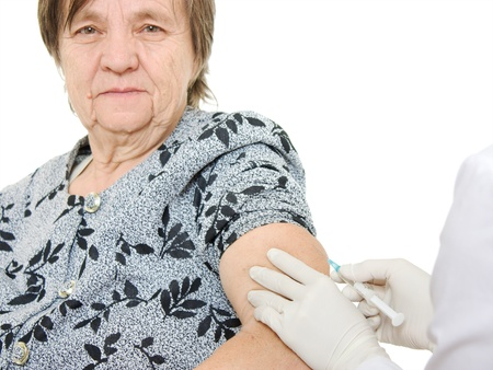 The doctor makes vaccination an old woman.