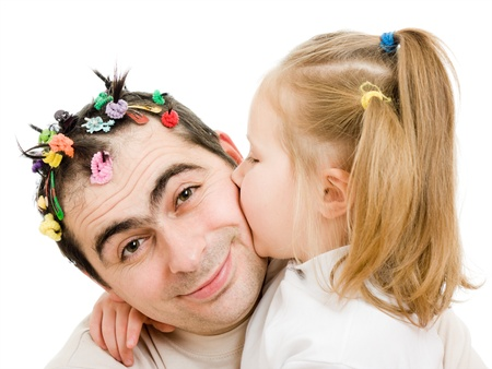 Daughter kissing her father on a white background.