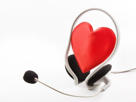 empatia: Los auriculares del corazón y un micrófono sobre un fondo blanco. Foto de archivo