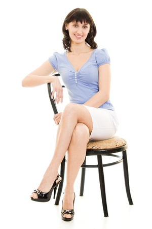 A woman in a blue shirt and white skirt sitting in a chair on a white background. photo