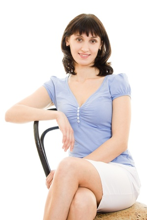 A woman in a blue shirt and white skirt sitting in a chair on a white background. Stock Photo - 11901899