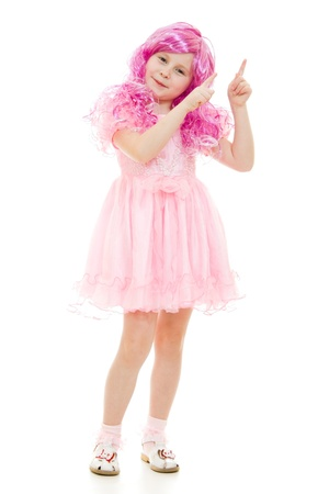 A girl with pink hair in a pink dress points to the top on a white background. photo