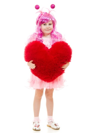 A girl with pink hair and a pink dress holding a pillow in the shape of heart. photo