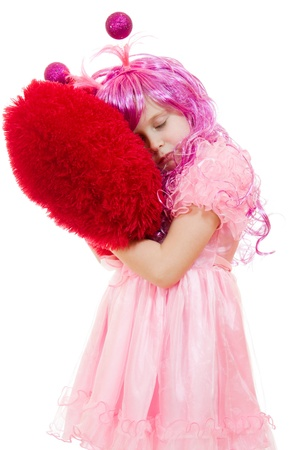 A girl with pink hair and a pink dress cuddle pillow in the form of the heart. photo