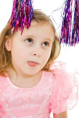 Funny girl in a pink dress with antennas on his head shows tongue on a white background. photo