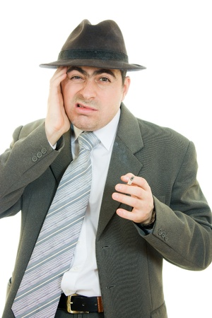 A businessman in a hat smokes on a white background.