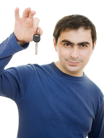 Young man holding keys in his hand, white background photo
