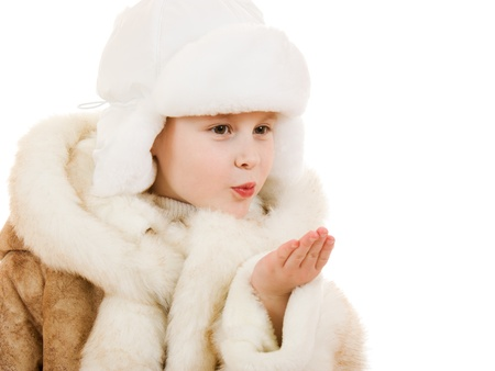 Girl in a sheepskin coat and cap sends a kiss on a white background  photo